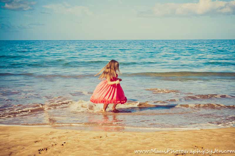 photography in maui with young girl playing in the ocean