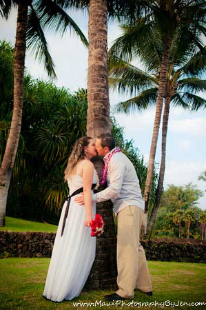 maui photographer with couple kissing around palm tree
