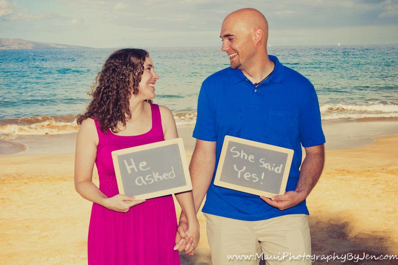 maui photographers with engaged couple holding sign