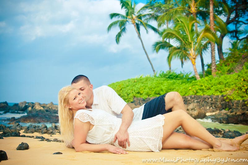 maui photographer with couple romantically laying on the beach